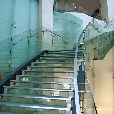 In questa foto mostriamo l'imponenza di una scala con gradini e parapetti in vetro e acciaio.