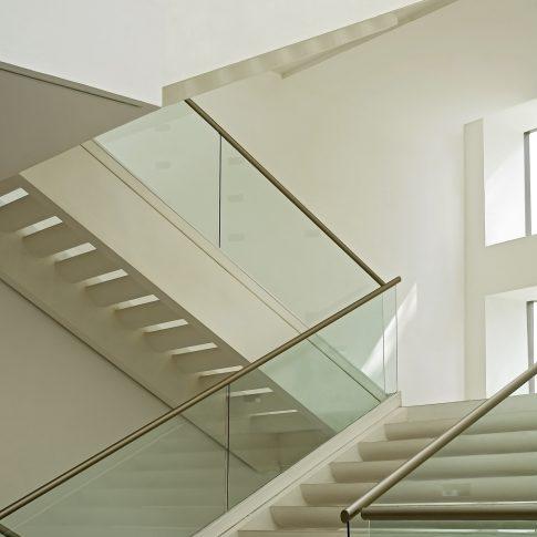 Un esempio di soluzione con corrimano e parapetti in vetro e acciaio, che valorizzano le scale di colore bianco.