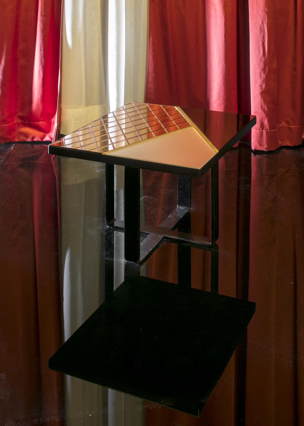 vb colors 04 – tavolino gioiello che riflette tutto ciò che c'è intorno attraverso forme che s'intrecciano al decoro geometrico inciso su specchio rosa.