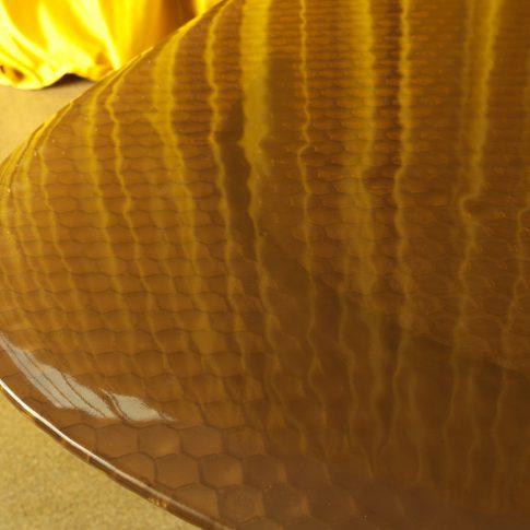 In questo piano di un tavolo in vetrofusione si nota in filigrana la trama a rete di pollo rimastra impressa nella lastra di vetro.